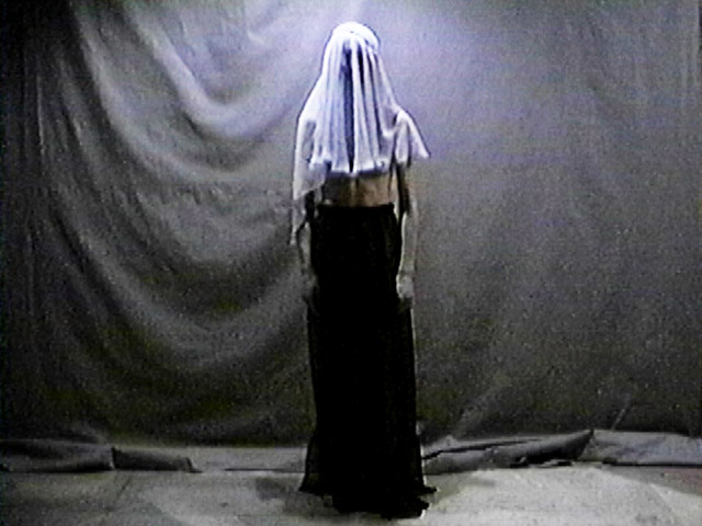 Performer standing against a dark backdrop, clothed in black from waist down, head covered with a white veil